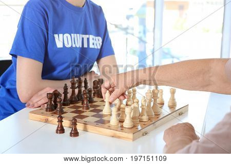 Young female volunteer playing chess with elderly woman in light room