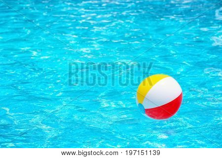 Colorful inflatable ball in blue swimming pool