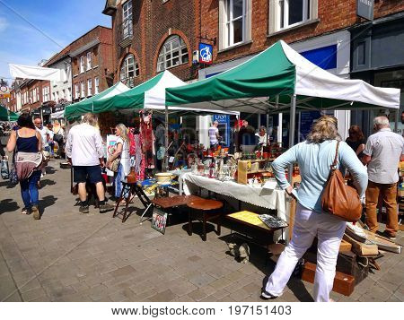 Winchester, UK - July 31, 2015:  Customers looking at antique and bric a brac stalls at the weekly street market in the city centre