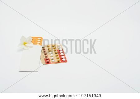 Two blister pack of birth control pills with flower on white background