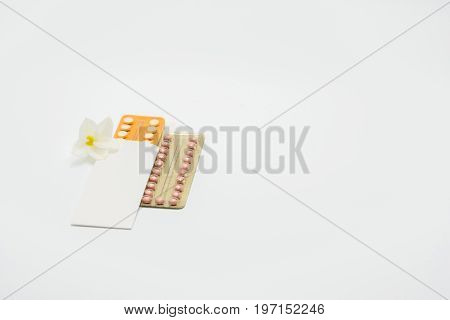 Two blister packs of birth control pills with flower on white background