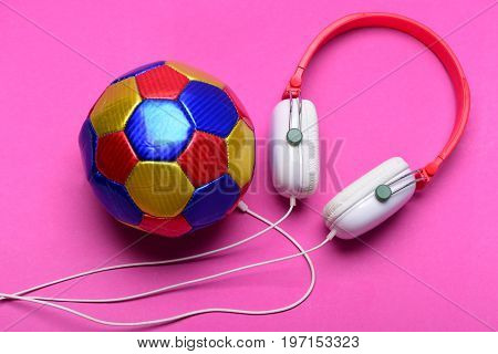 Modern earphones and football isolated on pink background. Music and sports equipment concept top view. Headset for music near soccer ball as player. Headphones in white red color with colorful ball