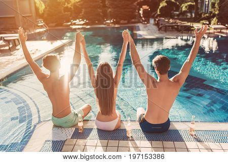 Back view of group of young friends is having fun near swimming pool together putting hands up and drinking beer.