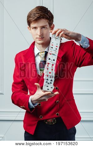 The magician in the red jacket does tricks with cards.
