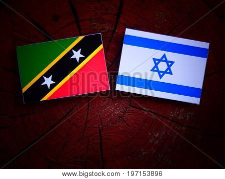 Saint Kitts And Nevis Flag With Israeli Flag On A Tree Stump Isolated