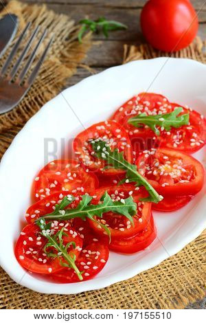 Fresh tomatoes, rucola and sesame seeds salad. Summer veggie salad on a white plate and burlap textile. Vertical photo