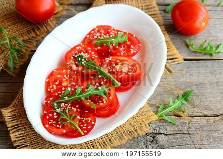 Easy tomatoes, rucola and sesame seeds salad. Bright veggie salad on a white plate and burlap textile. Fresh red tomatoes and green rucola on an old wooden table