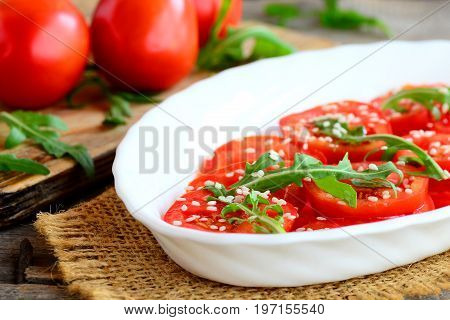 Fresh tomatoes, rucola and sesame salad. Summer vegetable salad on a white plate and burlap textile. Fresh tomatoes and rucola on a wooden table. Closeup