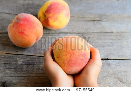 Small child holds a ripe peach in his hands. Sweet delicious peaches on an old wooden table. Encouraging healthy eating habits for kids