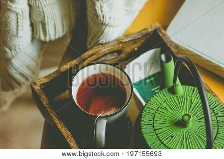 Off-white knitted sweater hanging over wooden chair mug with red fruit tea pot in tray by window old book hipster style autumn fall mood toned matte