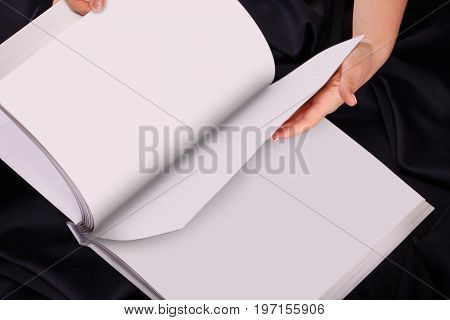 A woman or female two hands hold a empty blank or book or note diary spread or unfold top view studio.