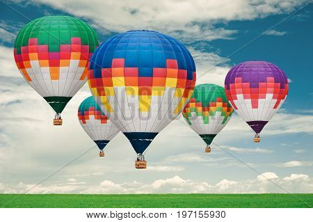 Colorful hot-air balloons flying over the field against cloudy sky