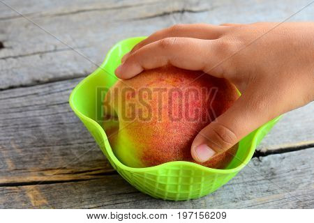 Small child takes a fresh peach in his hand. Sweet juisy peaches on a vintage wooden table. Natural food to support healthy growth and development of child