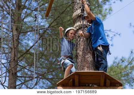 MEZIO, PORTUGAL - JULY 22, 2017: young adventurous kid prepares to slide on zip line thru the forest. July 22, 2017, Mezio, Portugal.