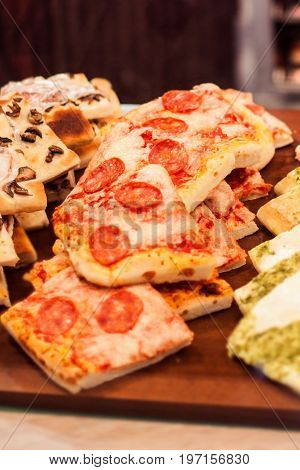 Pizza Take Away pieces on a stall in cafe Traditional Italian Focaccia with tomatoes black olives and cheese
