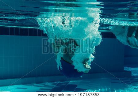 Men are jumping into the swimming pool. Men under water.