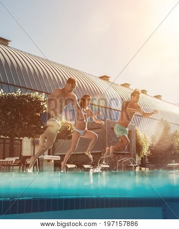 Young friends are having fun together. Jumping into the swimming pool.