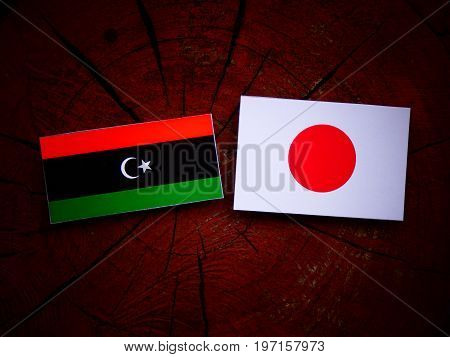 Libyan Flag With Japanese Flag On A Tree Stump Isolated