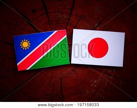 Namibian Flag With Japanese Flag On A Tree Stump Isolated