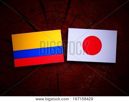 Colombian Flag With Japanese Flag On A Tree Stump Isolated