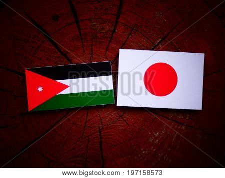 Jordanian Flag With Japanese Flag On A Tree Stump Isolated