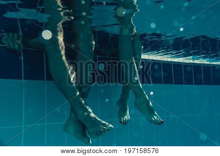 Underwater view of couple legs in the swimming pool