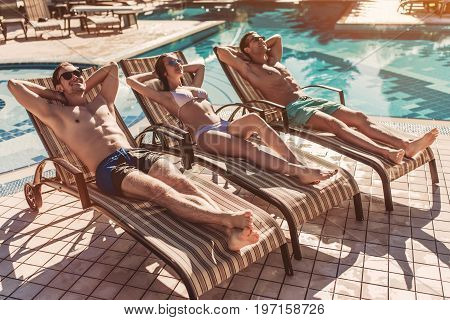 Group of young friends is lying on a chaise-longues near swimming pool and smiling. Having rest together.