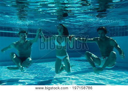 Underwater view of group of young friends are diving in swimming pool. Having fun together.