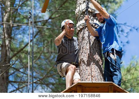 MEZIO, PORTUGAL - JULY 22, 2017: adventurous man prepares to  slide on zip lining thru the forest. July 22, 2017, Mezio, Portugal.