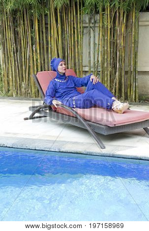 attractive woman in a Muslim swimwear burkini on a beach plank bed near the pool