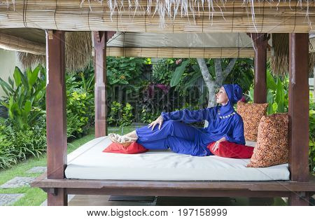 attractive woman in a Muslim swimwear burkini in gazebo for rest in a garden