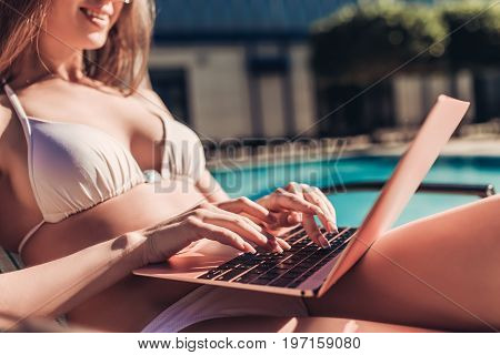 Working even on vacation! Cropped image of attractive young woman is lying on a chaise-longue near swimming pool with laptop.