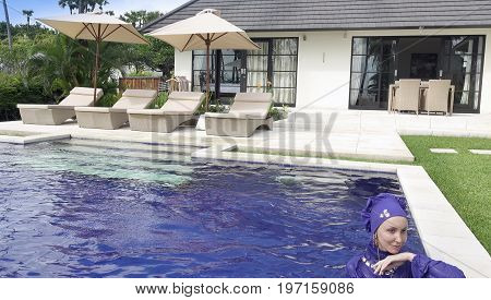 attractive woman in a Muslim swimwear burkini in the pool