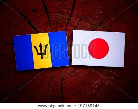 Barbados Flag With Japanese Flag On A Tree Stump Isolated