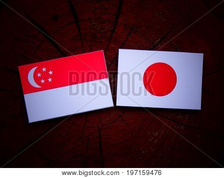 Singaporean Flag With Japanese Flag On A Tree Stump Isolated