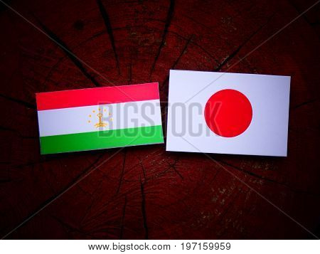 Tajikistan Flag With Japanese Flag On A Tree Stump Isolated