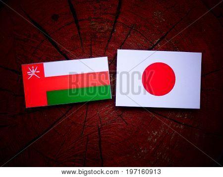 Omani Flag With Japanese Flag On A Tree Stump Isolated