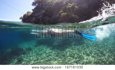 Half underwater close up, swimmer in flippers dives into the sea