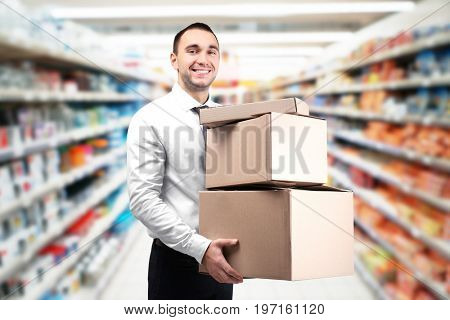 Young worker with cardboard boxes at storehouse. Wholesale and logistic concept