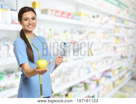 Nutritionist with fruit and clipboard at pharmacy