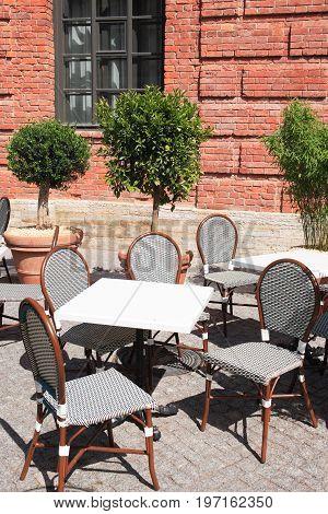 Empty street cafe near old brick building under sunlight