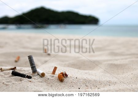 Cigarette butts and the ashtray on the beach near the sea.