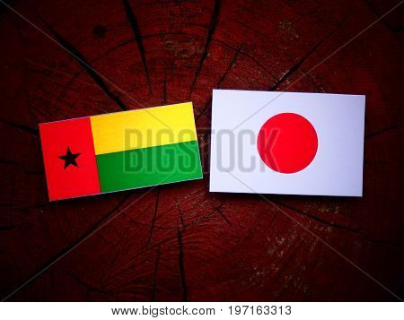Guinea Bissau Flag With Japanese Flag On A Tree Stump Isolated
