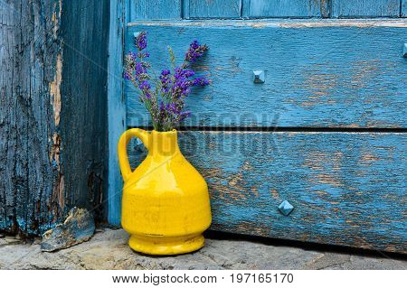 Lavender in a yellow kouvinum on a background of blue shabby door
