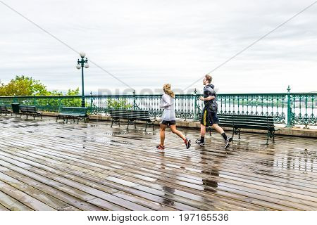 Quebec City, Canada - May 30, 2017: Two People Couple, Man And Woman, Running On Wet Dufferin Terrac