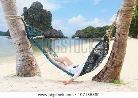 Tourists girls relaxing and lying on a hammock on the beach at Samui Island Thailand