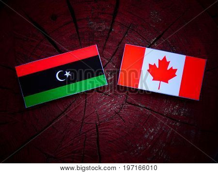 Libyan Flag With Canadian Flag On A Tree Stump Isolated