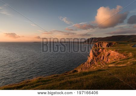 The cliffs that lead to Worms Head at Rhossili Bay on the far tip of the Gower peninsula, South Wales, UK