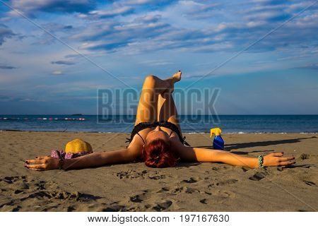 Young good looking tanned redhead laying on a sandy beach with arms resting and leg resting and happily posing with arms widespread with sun cream and hat on the side and blue sky and sea in the background during summer