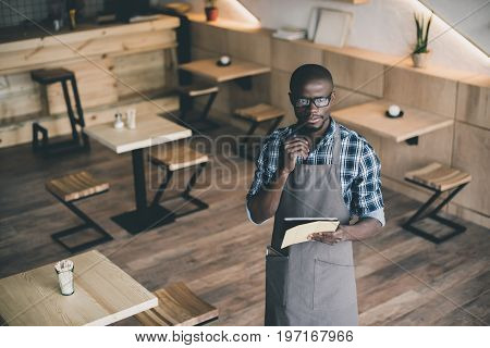 pensive african american waiter working and taking order in cafe